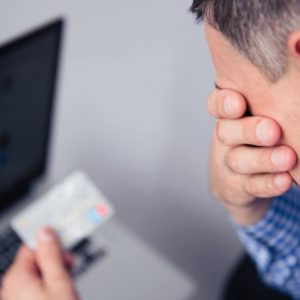 Upset man holding credit card in debt